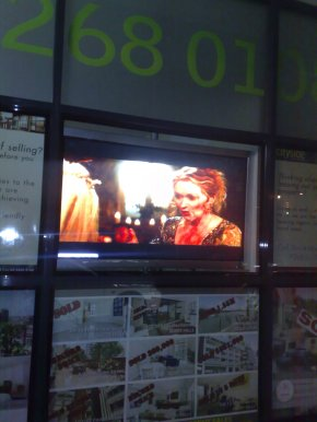 Mamma Mia screening in the window of a real estate agent in Sydney.