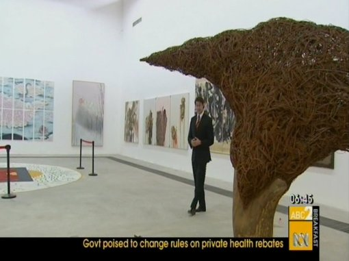 Reporter amidst art works.