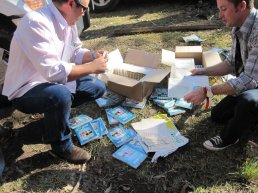Performer inserting inlays into DVD cases on the grass