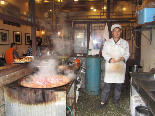 Man cooking a large pot of miscellaneous animal pieces