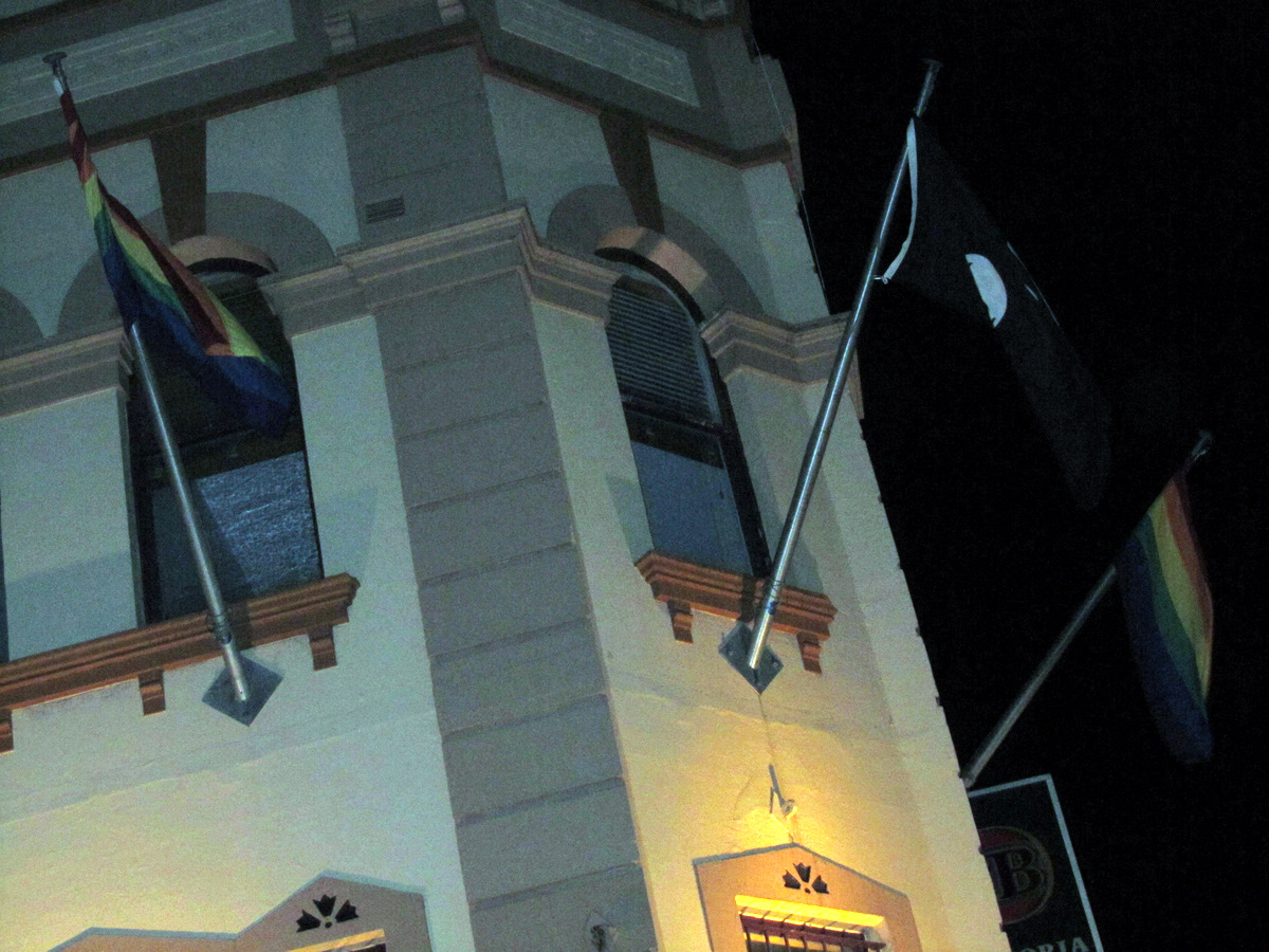 The Newtown Hotel is flying both the rainbow flag and the jolly roger.